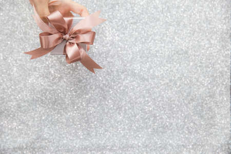 Female hands holding or giving a small gift box with copy space for text and silver glitter background.