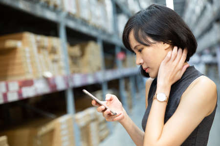 An asian woman doing shopping online via mobile phone in the warehouse. Cart and boxes on rows of shelves in warm light warehouse background.  Using for Mock up template for craft display of your design,Banner for advertise of product. Stockfoto
