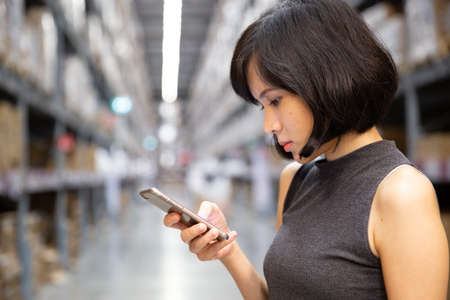 A beautiful woman using smart phone at the warehouse, searching or social networks concept, hipster lady typing an sms message.