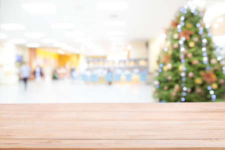 Empty wooden table top over Blurred abstract of decorated Christmas tree with toys, gift box and bauble inside the office building or hospital. Chritmas and Happy New year concept. bokeh lights.