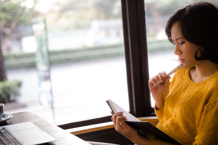 Young business woman in yellow dress sitting at table in cafe and writing in notebook. On table is laptop, smartphone and cup of coffee. Freelancer working in coffee shop. Student learning online.