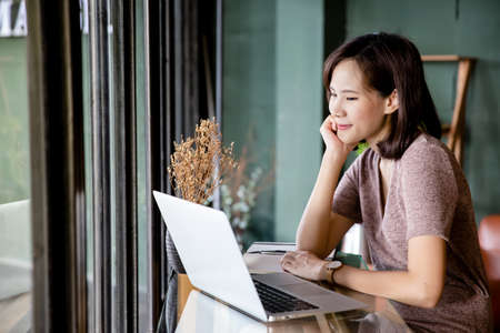 Beautiful young Asian woman working at a coffee shop with a laptop. Female freelancer connecting to internet via computer. Casual Thinking Browsing Concept.
