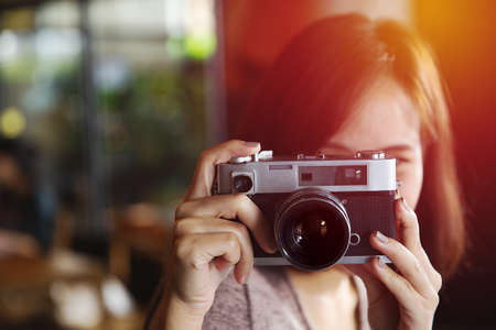 Pretty young hipster woman making photo. Retro photographer. Modern urban girl has fun with vintage photo camera in the cafe or restaurant. City lifestyle concept. Vintage Filter. 版權商用圖片