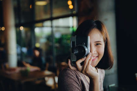 Pretty young hipster woman making photo. Retro photographer. Modern urban girl has fun with vintage photo camera in the cafe or restaurant. City lifestyle concept. Vintage Filter. Stockfoto