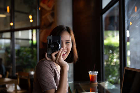 Pretty young hipster woman making photo. Retro photographer. Modern urban girl has fun with vintage photo camera in the cafe or restaurant. City lifestyle concept.