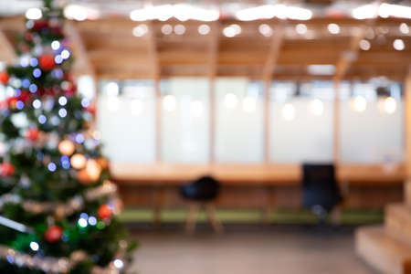 Blurred abstract of decorated Christmas tree with toys, gift box and bauble inside the office building. Chritmas and Happy New year concept. Stock Photo