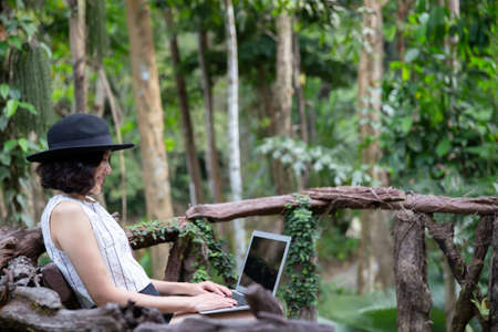 Happy asian woman sitting in the forest using laptop computer. Stockfoto