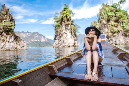 A beautiful asian woman travelling by long tail boat to the island