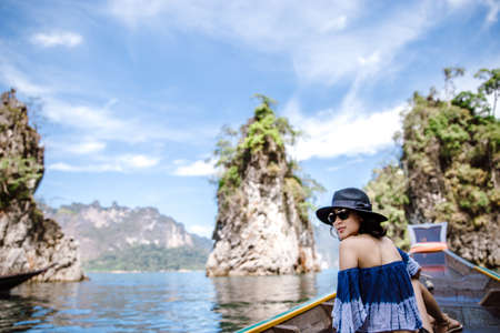 Back side of a woman sitting on long tail boat and enjoying the view of ocean and islands.