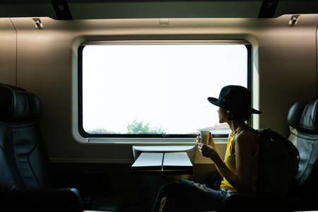 A beautiful hipster asian woman travelling on the train. Sitting on the black leather cozy comfort seat in the business class boky of the train in Europe and holding camera, wearing black hat.Tourist travel concept. Stock Photo