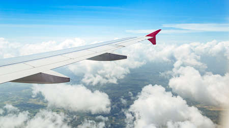 View of window on bright sky background at flying airplane and city from top view.  the wing of the aircraft against the sky, clouds