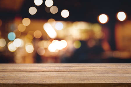 Empty dark wooden table in front of abstract blurred bokeh background of restaurant, pub or bar. Blurred background for product display or montage your products with several concept idea and any occasion. Banco de Imagens