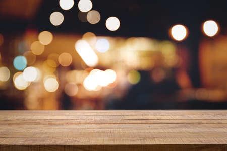 Tavolo in legno scuro vuoto davanti a sfondo bokeh sfocato astratto di ristorante, pub o bar. Sfondo sfocato per la visualizzazione del prodotto o il montaggio dei tuoi prodotti con diverse idee concettuali e ogni occasione. Archivio Fotografico