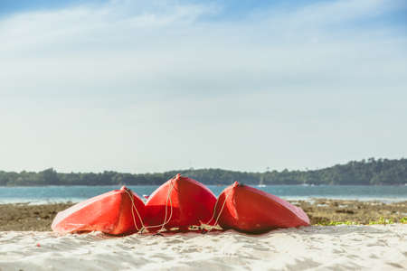 Red kayaks on the tropical beach, Active rest, sport. A few cannoe stand on a sandy beach. summer concept