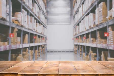 Leere Holztischplatte auf unscharfem Lagerhintergrund für die Anzeige Ihrer Produkte.