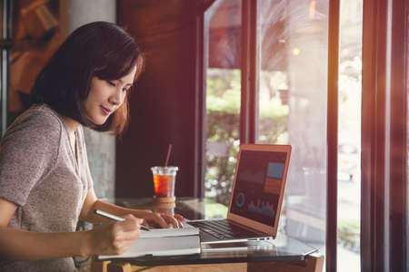 Isolated mockup image of laptop and Young business woman in casual dress sitting at table in cafe and writing in notebook. Freelancer working in coffee shop. Student learning online. Stockfoto