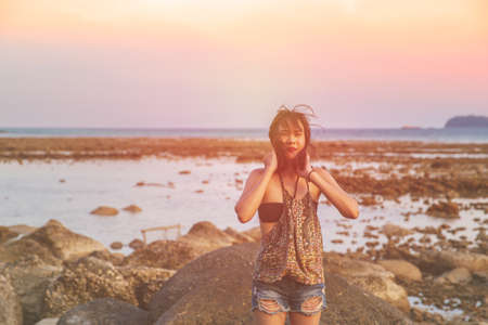 Abstract Young woman in casual style fashion Standing on the beach. Relaxing and enjoy holiday at tropical paradise beach. Girl in summer vacation. Summer vibes. Vintage film grain filter style. Stockfoto