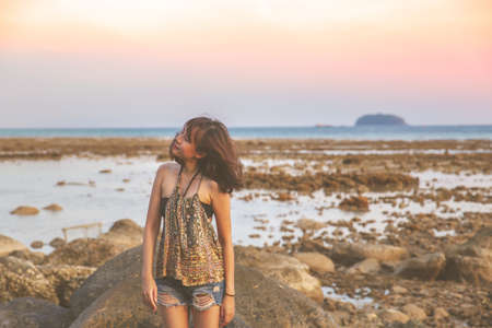 Young woman in casual style fashion Standing on the beach. Relaxing and enjoy holiday at tropical paradise beach. Girl in summer vacation. Summer vibes.