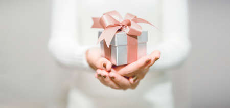 Woman hands with white sweater holding a small gift box for special event with copy space. Christmas, birthday or new year concept.