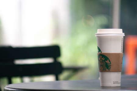 Bangkok, Tajlandia – 1 września 2019: wysoka filiżanka kawy Starbuck na stole na świeżym powietrzu. Starbucks zabrać filiżankę kawy z logo, tło wnętrza bokeh.