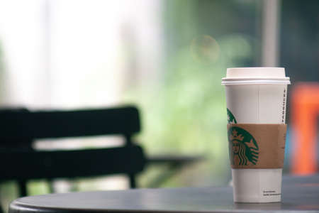 Bangkok, Thailand - Sep 1, 2019: a tall cup of Starbuck coffee on the outdoor table. Starbucks take away coffee cup with logo, bokeh interior background.