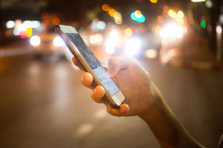 Using her Mobile Phone in the pub or  restaurant, night light bokeh Background