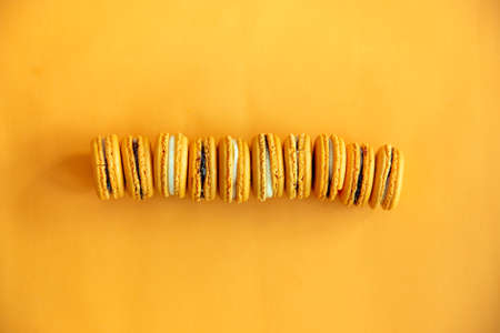 Top view of tasty orange yellow macarons. Concepts ideas background on yellow paper, flatlay and copy Space