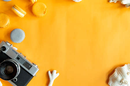 Top view of tasty orange yellow macarons and camera. Concepts ideas background on yellow paper, flatlay and copy Space