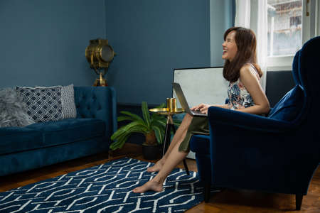 Cozy young asian woman freelancer sit on modern sofar and typing laptop with green palm tree in living room at home. Work at home or summer concept. Stockfoto