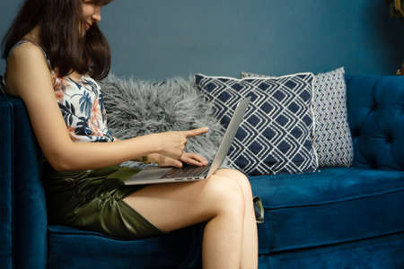 Cozy young asian woman freelancer sit on modern sofar and pointing laptop with green palm tree in living room at home. Work at home or summer concept. Stockfoto
