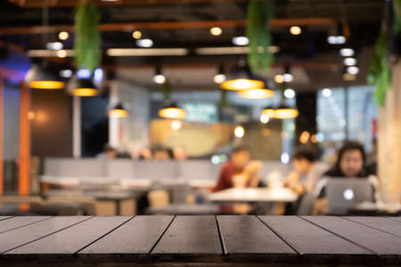 Empty wooden table in front of Blur background of coffee shop or restaurant interior abstract. Using for Mock up template for display of your design or montage  products. Stockfoto