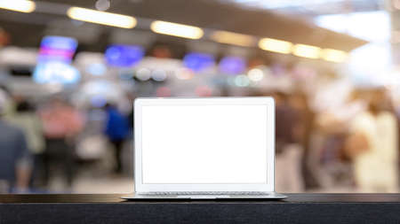 Laptop with blank screen on black table in airport, clipping path inside. Can be used for mock up template or design key visual layout for advertise of product.