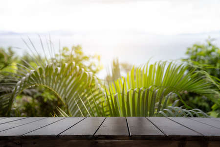 Wood table top (Bar) with blur on green palm leaves or tree in tropical forest with sky and sea at background - Using for Mock up template for display of your design.