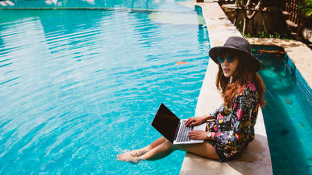 Hipster woman using laptop working as freelancer by the pool in summer time. Stockfoto