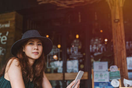 Young beautiful asian woman working in loft cafe or office. Holding smart phone for browsing and searching internet wifi. Business woman or freelancer working on new project.
