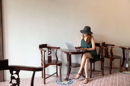 Asian woman wear hat and using laptop in coffee shop cafe, warm color. Freelancer working at a cafe with a laptop Stockfoto