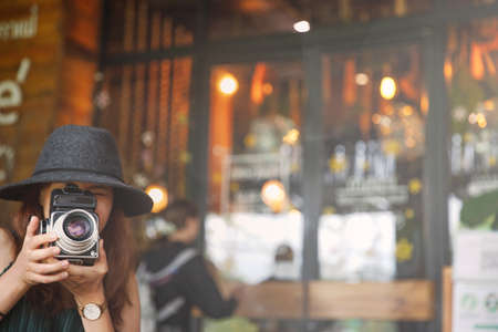 Young beautiful asian woman making a photo of cafe or restaurant by old camera. copy space