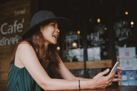 Asian woman wear hat and using laptop in coffee shop cafe, warm color.