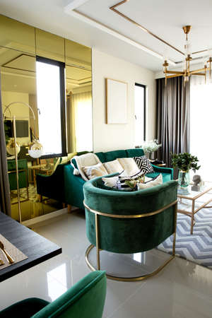 Modern scandinavian living room interior with dark green sofa, design commode, leaf in vase, cozy pillow, and elegant accessories. Template. Stylish home decor. Stockfoto