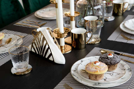 Modern scandinavian living room interior with dining table with mable plates and muffin, design commode, leaf in vase, golden cutlery, and elegant accessories. Template. Stylish home decor.