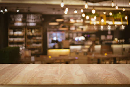 Blank wooden bar counter with defocused background and bottles of restaurant, bar or cafeteria background /for your product display Stockfoto