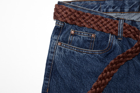 Classic jeans with five pockets close-up. jeans with a woven belt of brown leather and coarse thick threads. vintage blue textured denim fabric on pure white background. Fashionable casual style