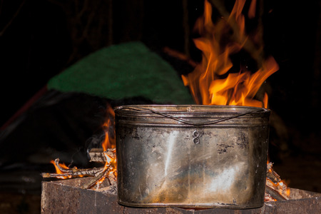 dinner at the campsite. kettle on a burning fire, fire, smoke. cooking on a trip. wild rest.