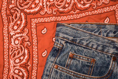 Classic jeans with five pockets close-up. Paisley patterned bandana, classic orange and white neckerchief, biker headscarf. Rough denim. Fashionable casual style, hippie, western, boho. Clothing for the festival. Imagens