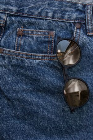 Round sunglasses on a denim texture background. round yellow glasses in the front pocket of jeans. Rough denim fabric. Classic jeans five pockets close-up. Fashionable round glasses in your pocket. Fashion casual style.