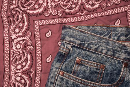 Classic jeans with five pockets close-up. Paisley patterned bandana, classic red and white neckerchief, biker headscarf. Rough denim. Fashionable casual style, hippie, western, boho. Clothing for the festival.