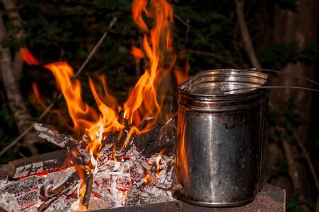 dinner at the campsite. kettle on a burning fire, fire, smoke. preparing a meal on a trip. wild rest.
