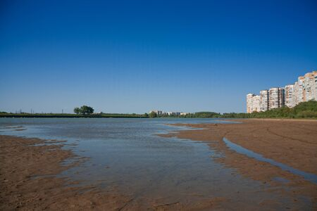border of a large multi-story city and countryside. tall houses on the banks of a shallow river. the concept of urban expansion and the destruction of small rural settlements