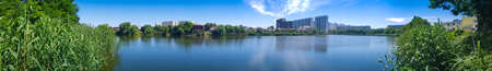 panorama city high-rise buildings on the shore of the lake thickets of green trees bushes. rest within the city city infrastructure park square recreation area