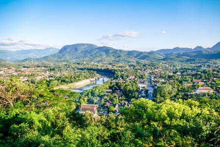 プーシ山からのルアンプランラオスビュー。東南アジア、プーシ山の頂上からの町と周辺の田園地帯の眺め
